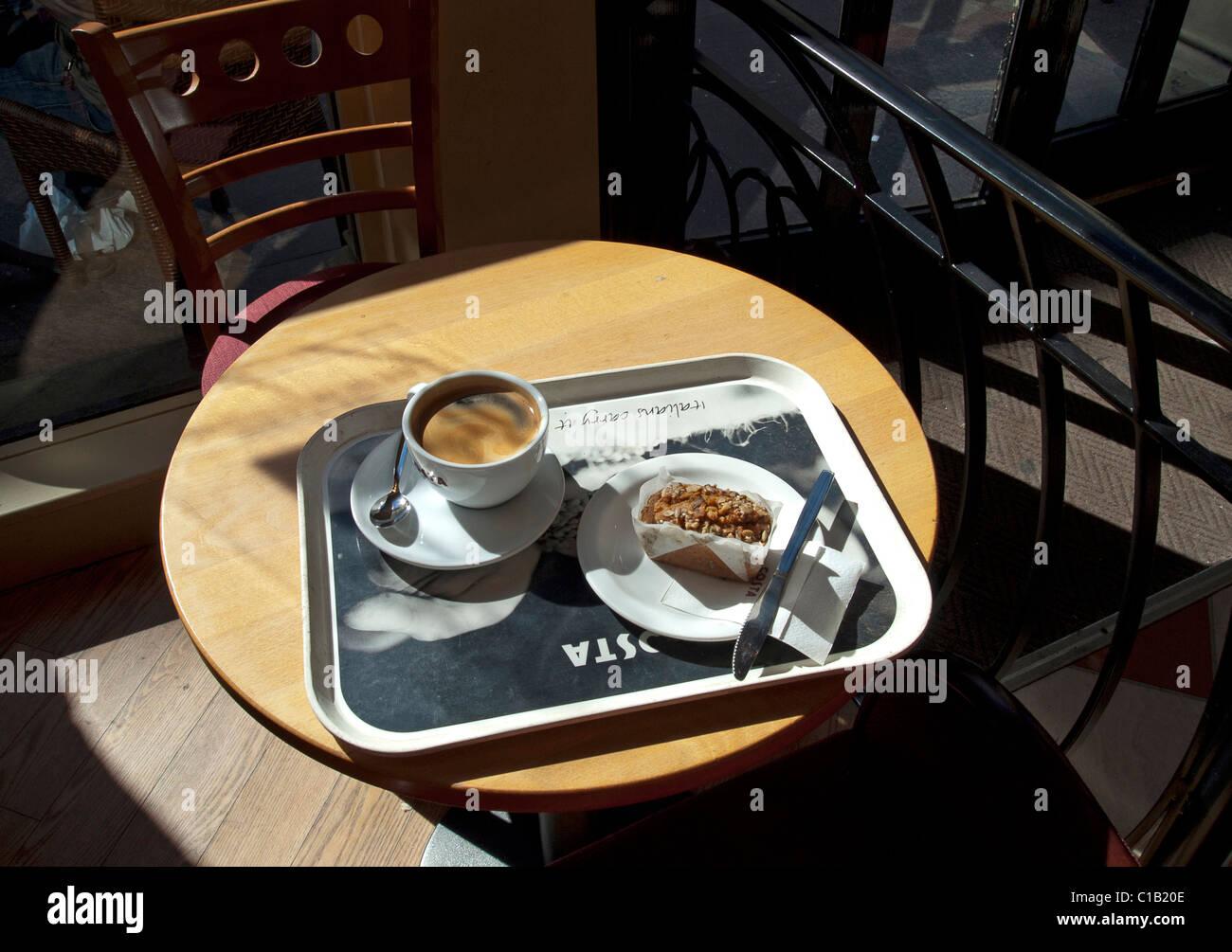 Tasse Kaffee und Kuchen auf Tablett verzehrfertig ist Stockbild