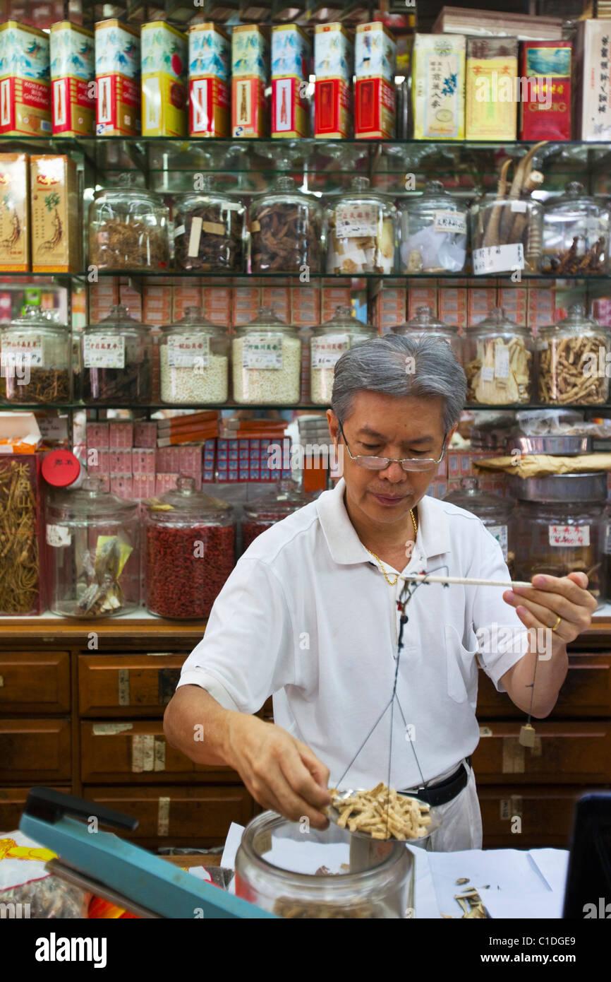 Ein Ladenbesitzer wiegt Zutaten in einem Shop für traditionelle chinesische Medizin.  Chinatown, Singapur Stockbild