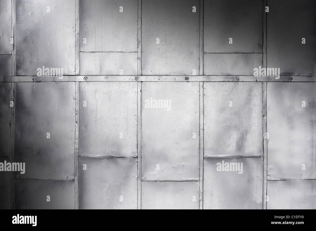 Metallplatten auf industrielle Tür oder Wand schräg beleuchtet Stockbild