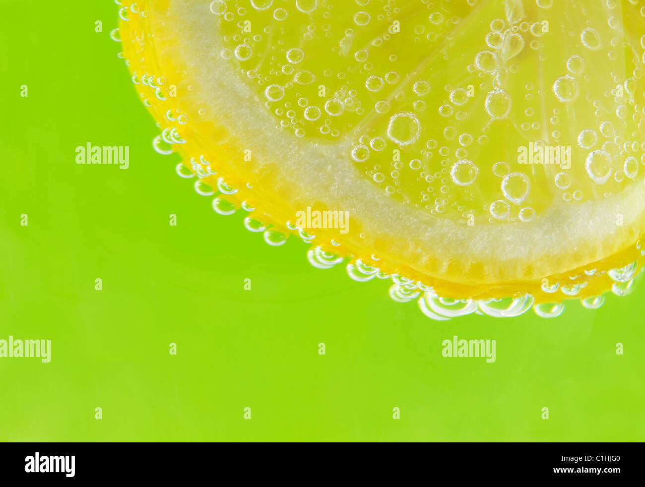 Eine Scheibe Zitrone ist mit Selters Luftblasen gegen einen frischen, Frühling grünen Hintergrund akzentuiert. Stockbild