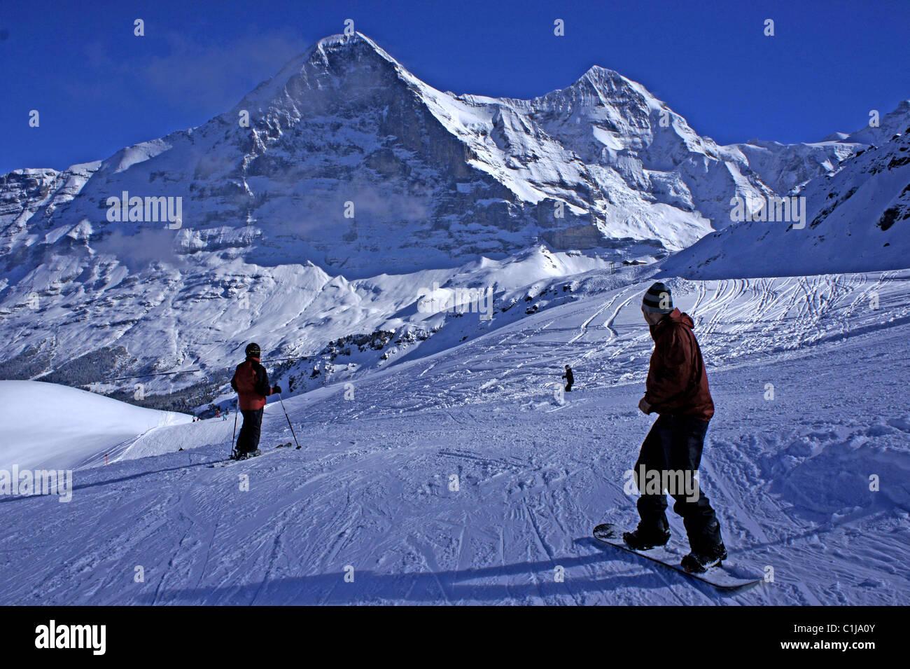 Skifahrer auf den Pisten Skiarea männlichen oben Grindelwld mit Mtns. Eiger und Monch, Berner Alpen, Schweiz Stockbild