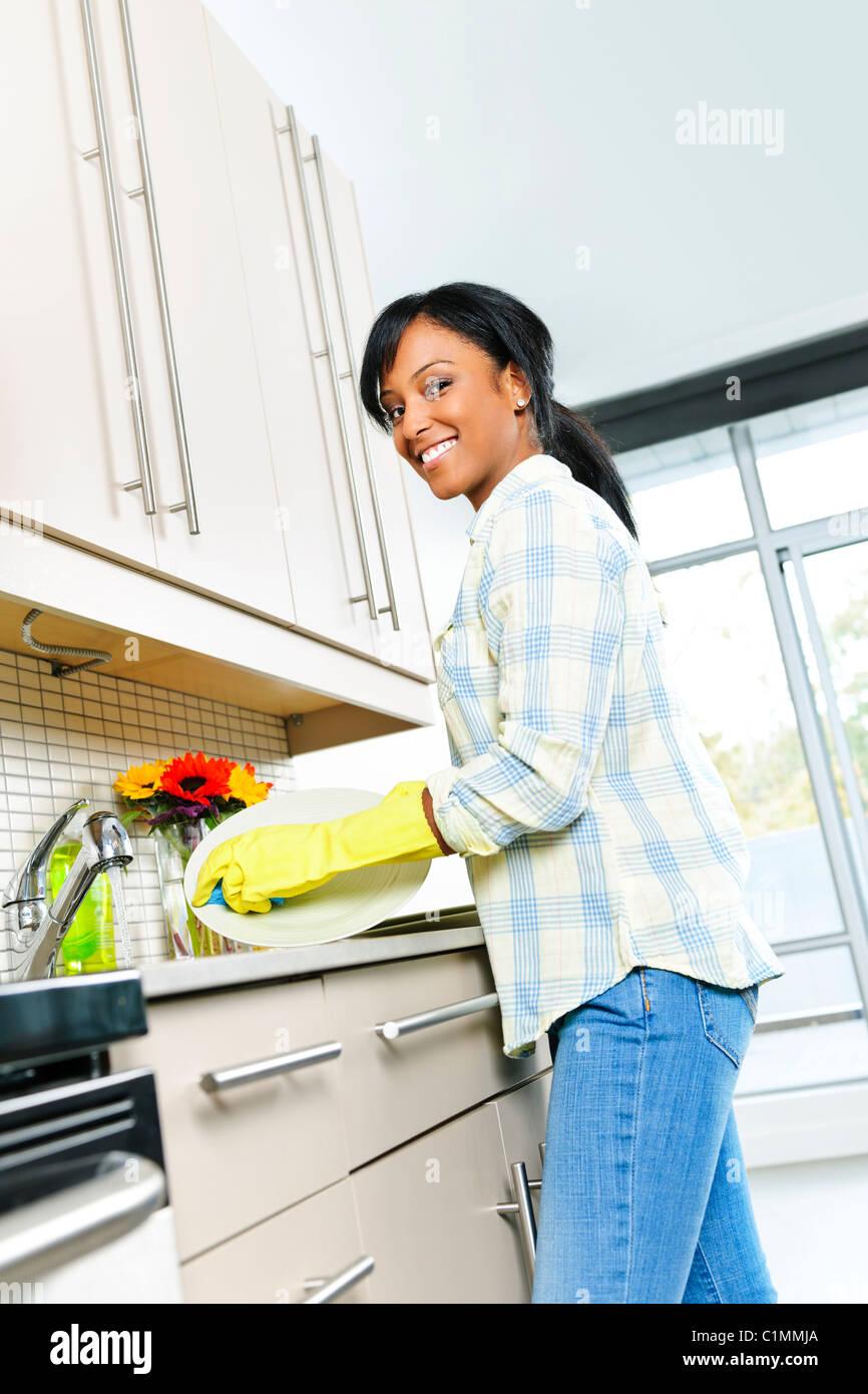 Glücklich lächelnde junge schwarze Frau genießen beim Abwasch in der Küche Stockbild