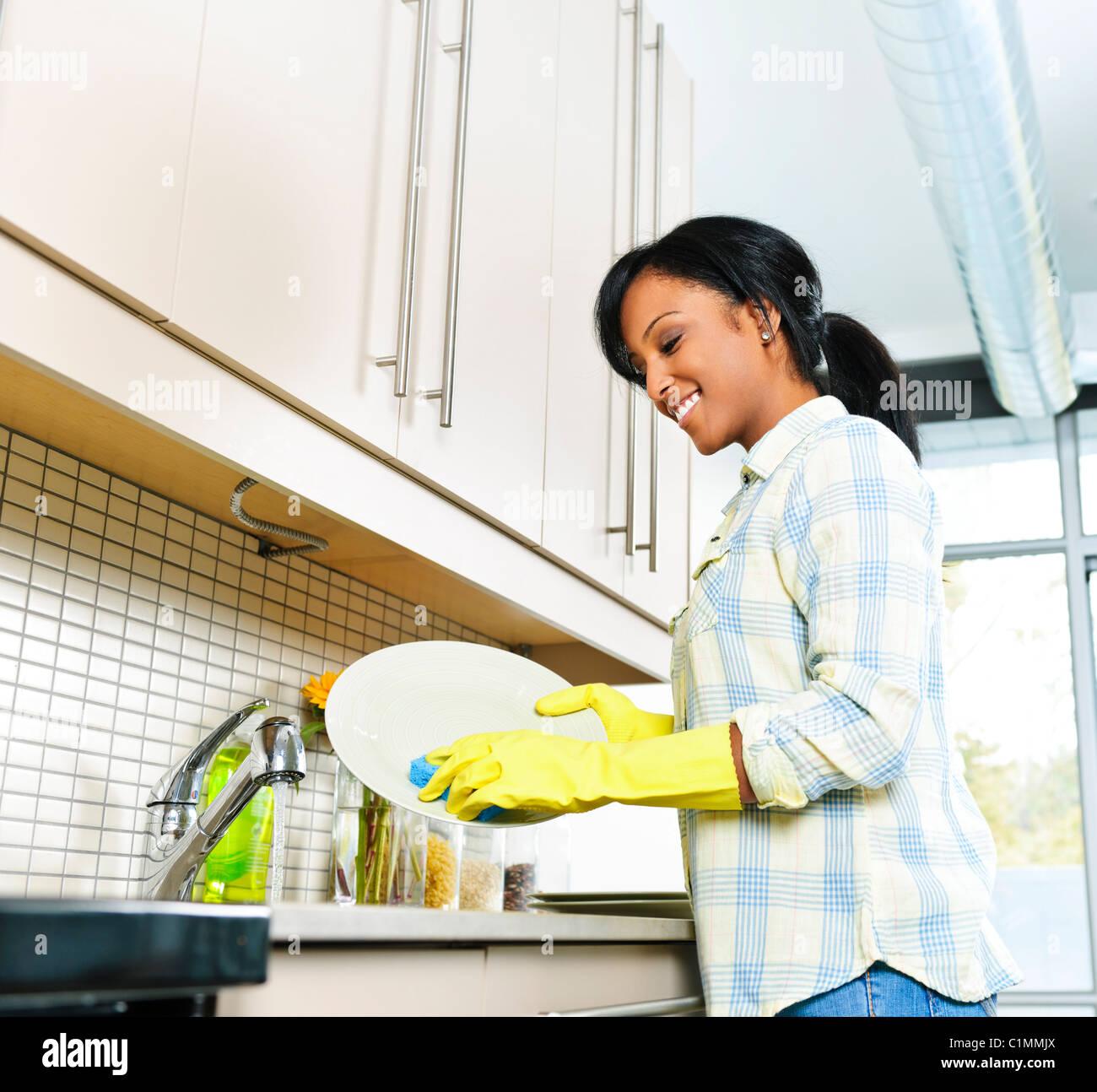 Lächelnde junge schwarze Frau beim Abwasch in der Küche Stockbild