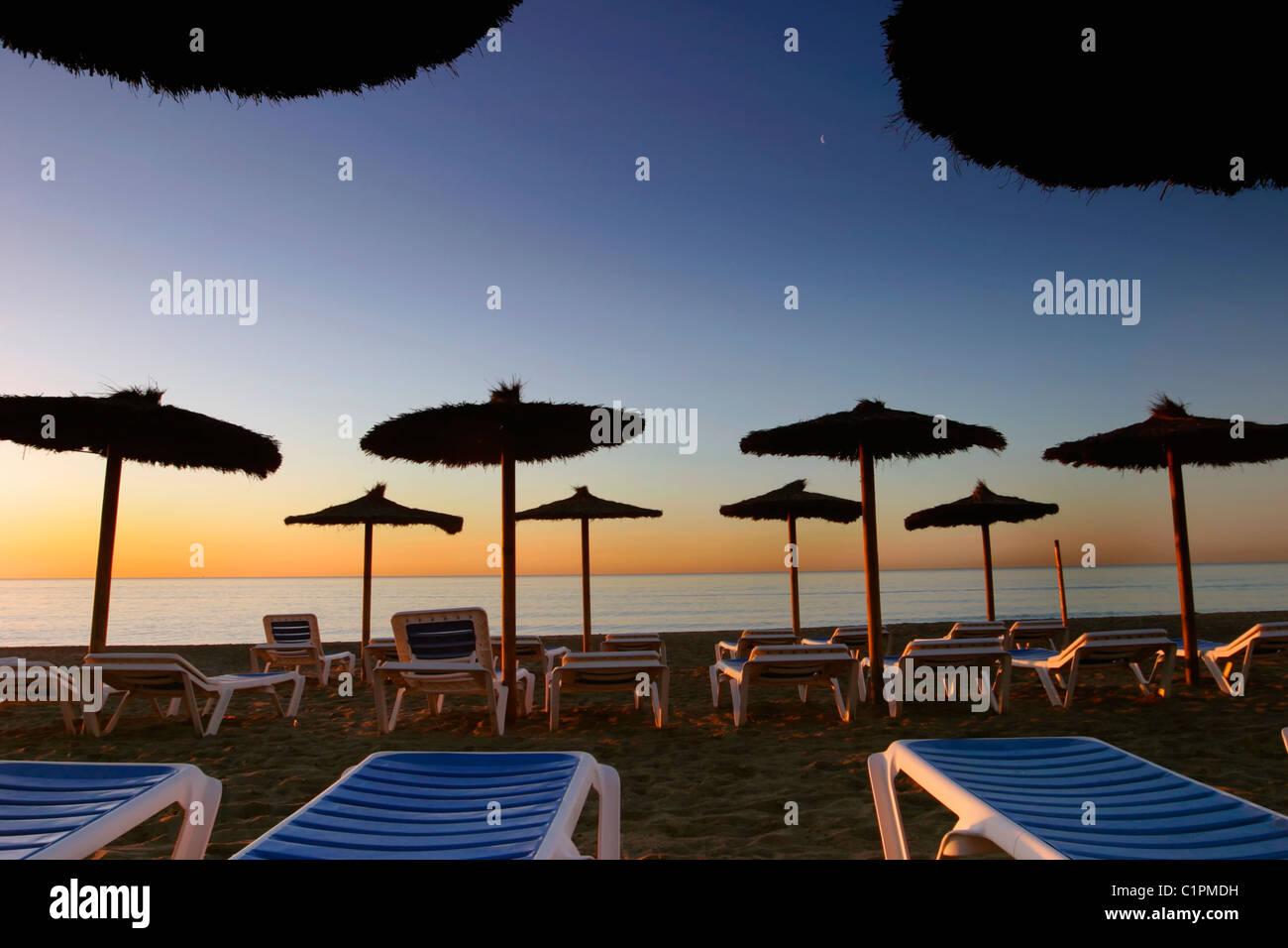 Torremolinos, Provinz Malaga, Costa Del Sol, Spanien. Sonnenaufgang mit Sonnenschirmen und Liegestühlen am Stockbild