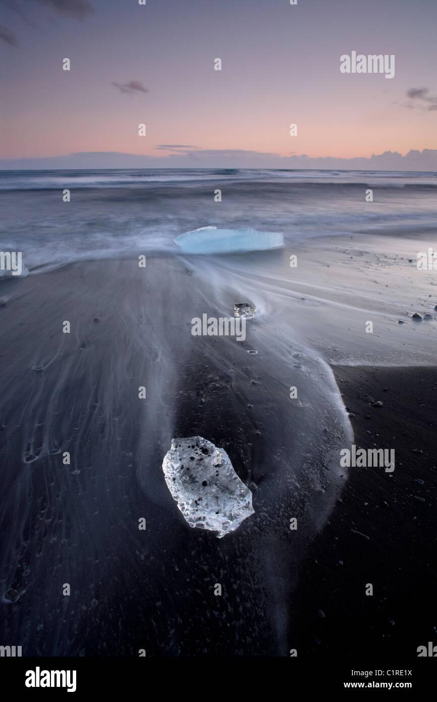 Eisberge am schwarzen Strand mit den Gezeiten waschen um sie herum in Island Stockfoto