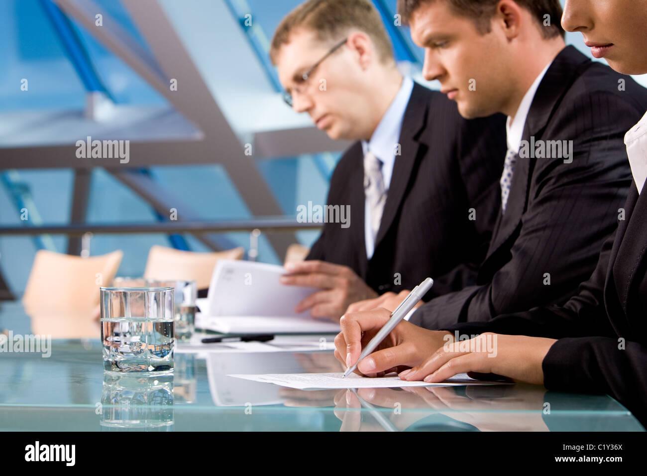 Reihe von ernsthaften Geschäftsleuten Notizen während der Konferenz Stockfoto