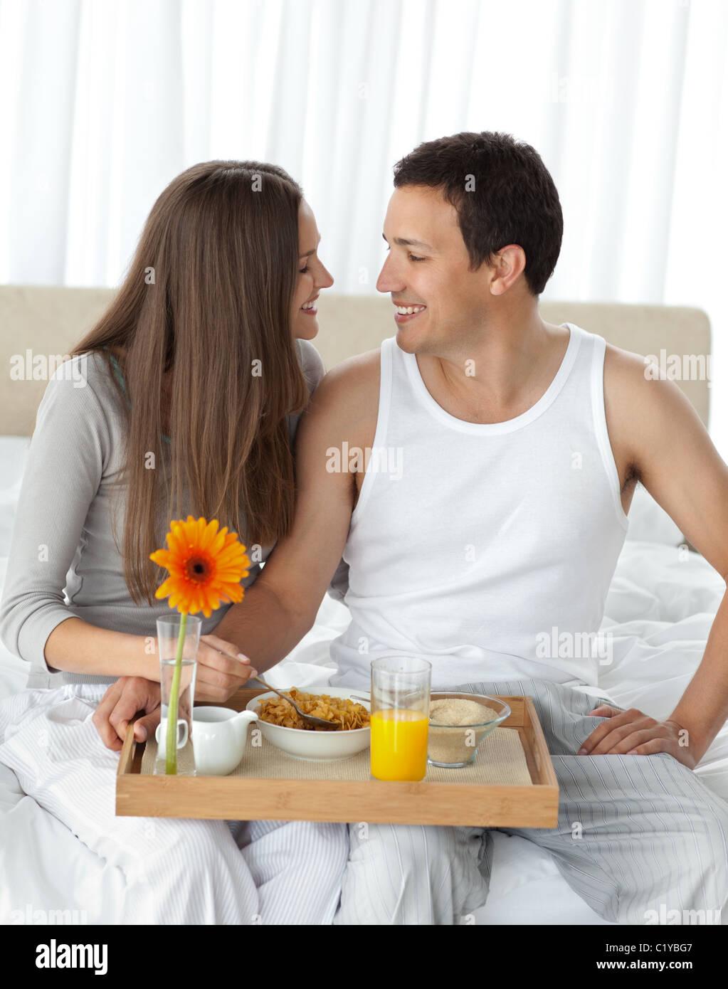 Leidenschaftliche Paare mit ihrem Frühstück sitzen auf dem Bett Stockbild