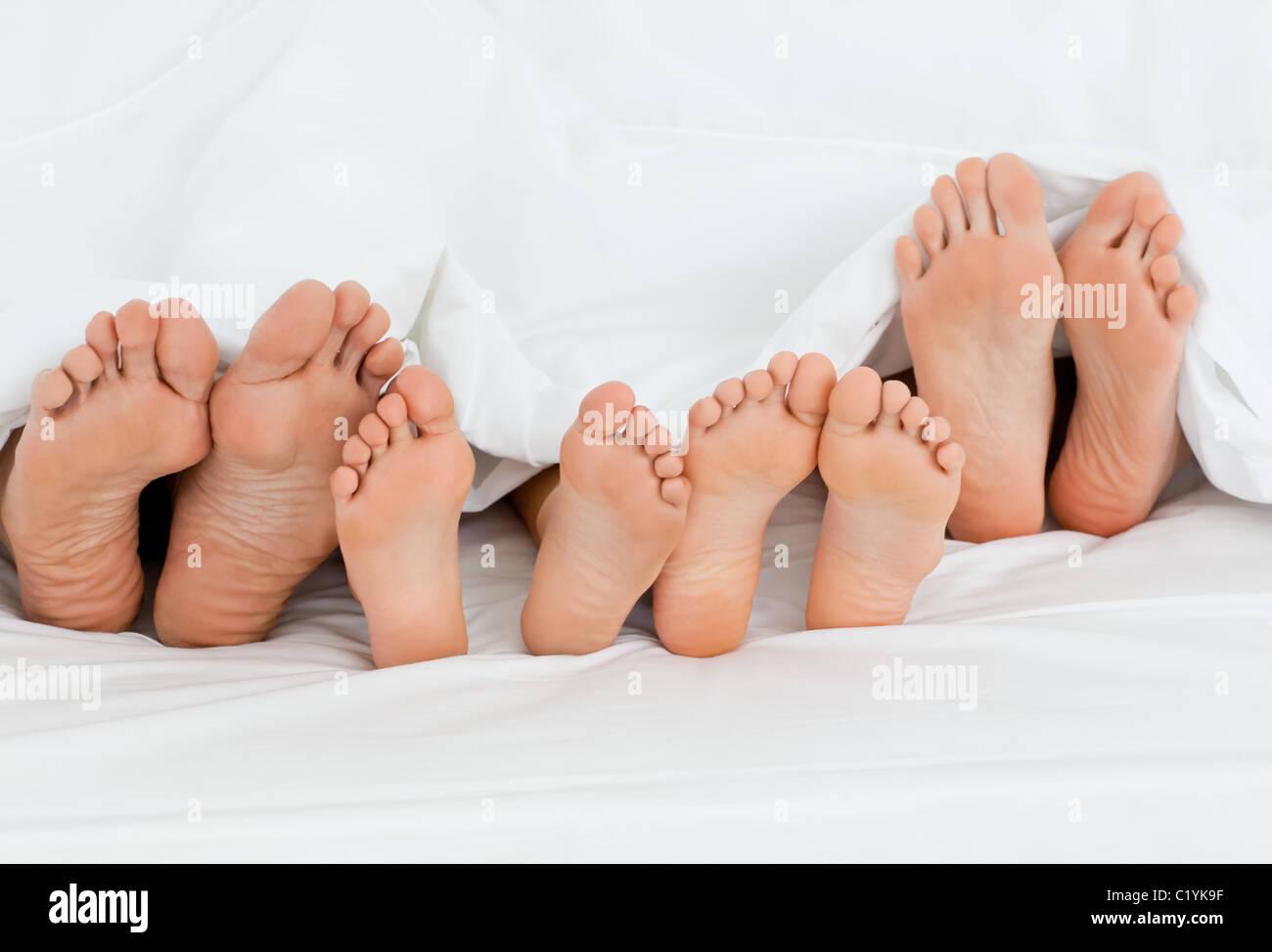 Familie auf dem Bett zu Hause mit ihren Füßen zeigen Stockbild