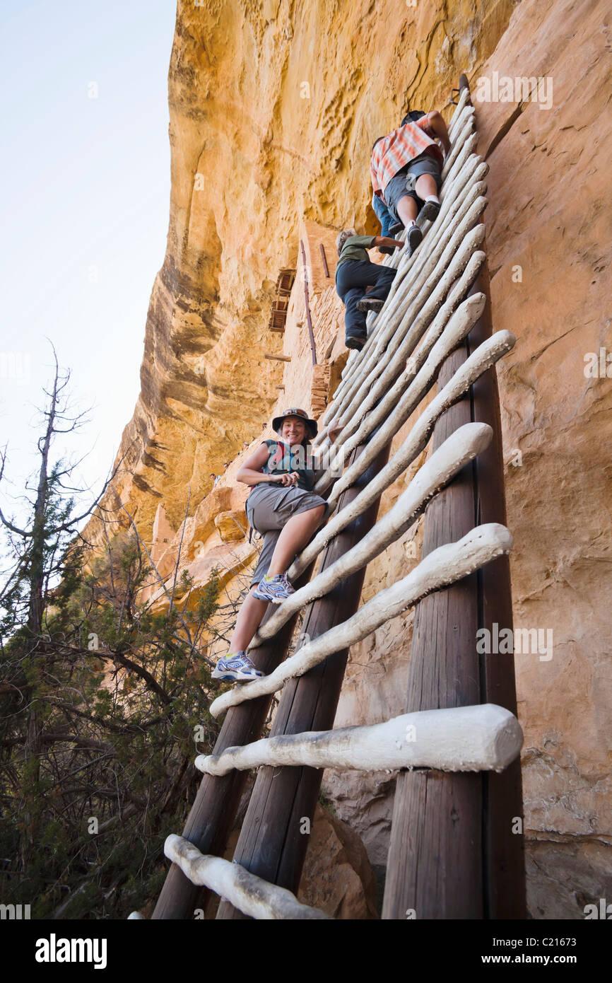 Eine Frau posiert für ein Foto auf einer Leiter hinauf zum Balcony House Cliff bewohnen in Mesa Verde Nationalpark, Stockbild