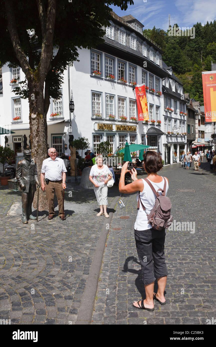 Touristen fotografieren durch eine Statue eines alten Mannes im Zentrum von Monschau, Aachen, Nordrhein-Westfalen, Stockfoto