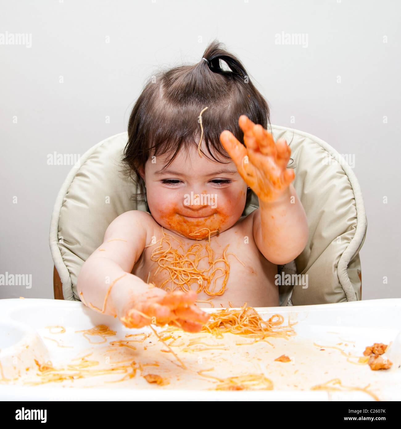 Glückliches Baby Spaß Essen chaotisch slapping Hände in Angel Hair Pasta Spaghetti rot marinara Tomatensauce bedeckt. Stockfoto