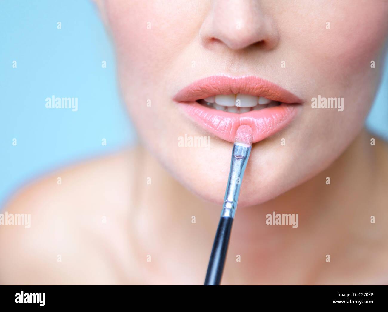 Frau Anwendung Lippenstift mit Make-up Pinsel - Nahaufnahme Stockfoto
