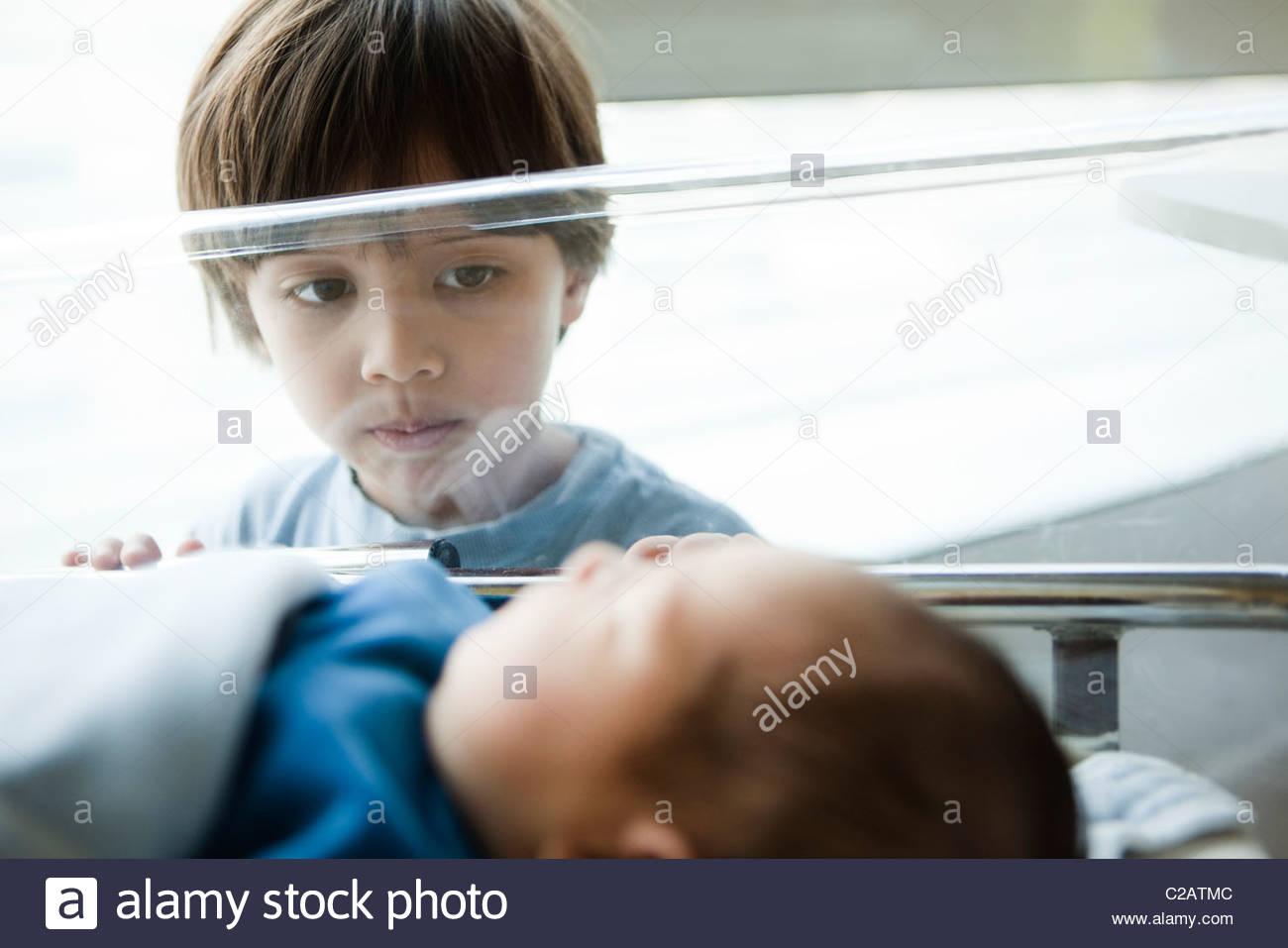 Kleiner Junge starrte auf Neugeborenen Geschwister im Krankenhaus Krippe Stockbild