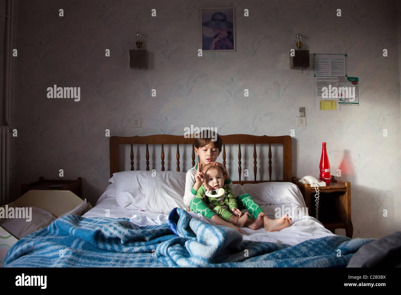 Kleiner Junge sitzt mit seiner kleinen Schwester auf Hotelbett Stockbild