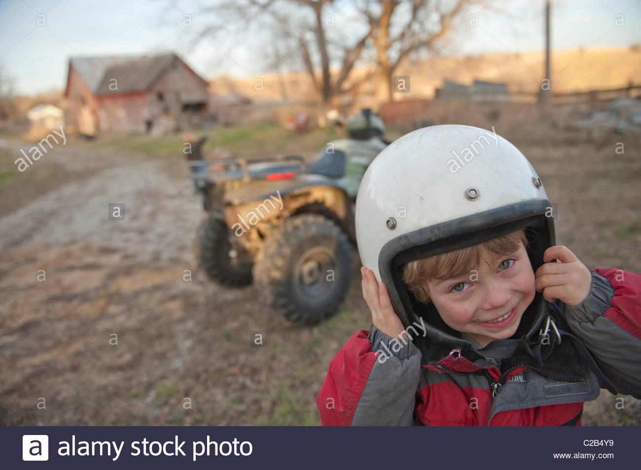 Ein Junge trägt einen Schutzhelm auf einer Farm in Dunbar, Nebraska. Stockbild
