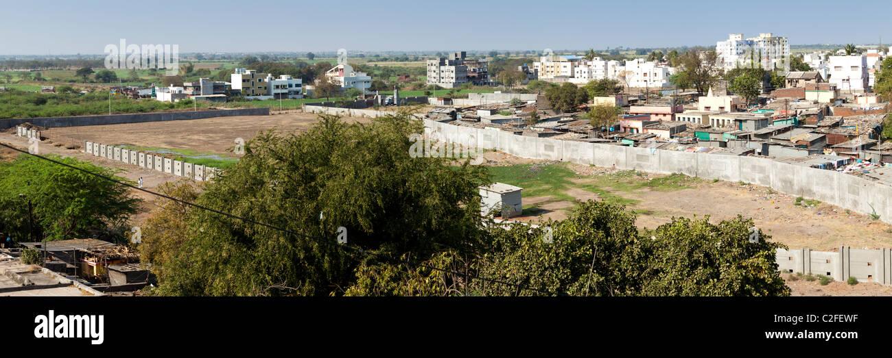 Panorama von einem indischen Elendsviertel. Eine Betonwand verhindert eine weitere Ausbreitung. Sholapur Maharastra Stockbild