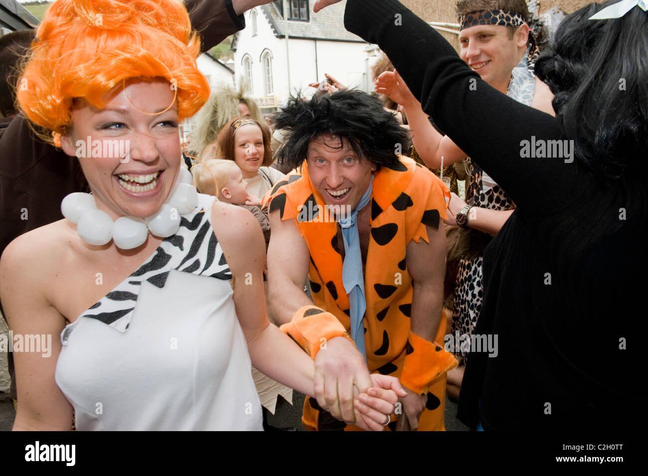 Ed Robinson (34) (Fred) und Gayle Watson (29) (Thelma) in ihre Familie Feuerstein themed Hochzeit in Combe Martin, Stockbild