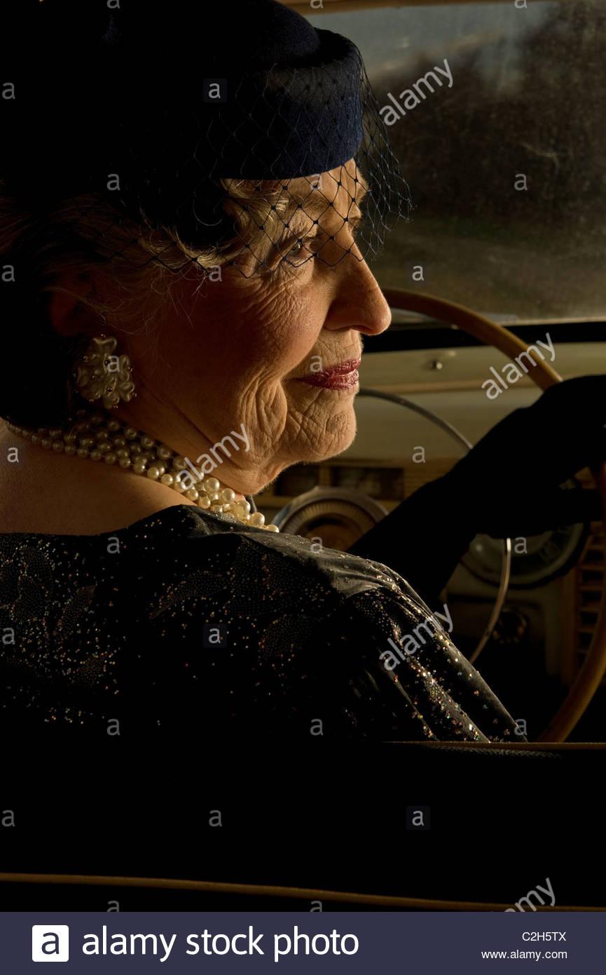 Reife Frau Senior ist einen Oldtimer fahren Stockbild