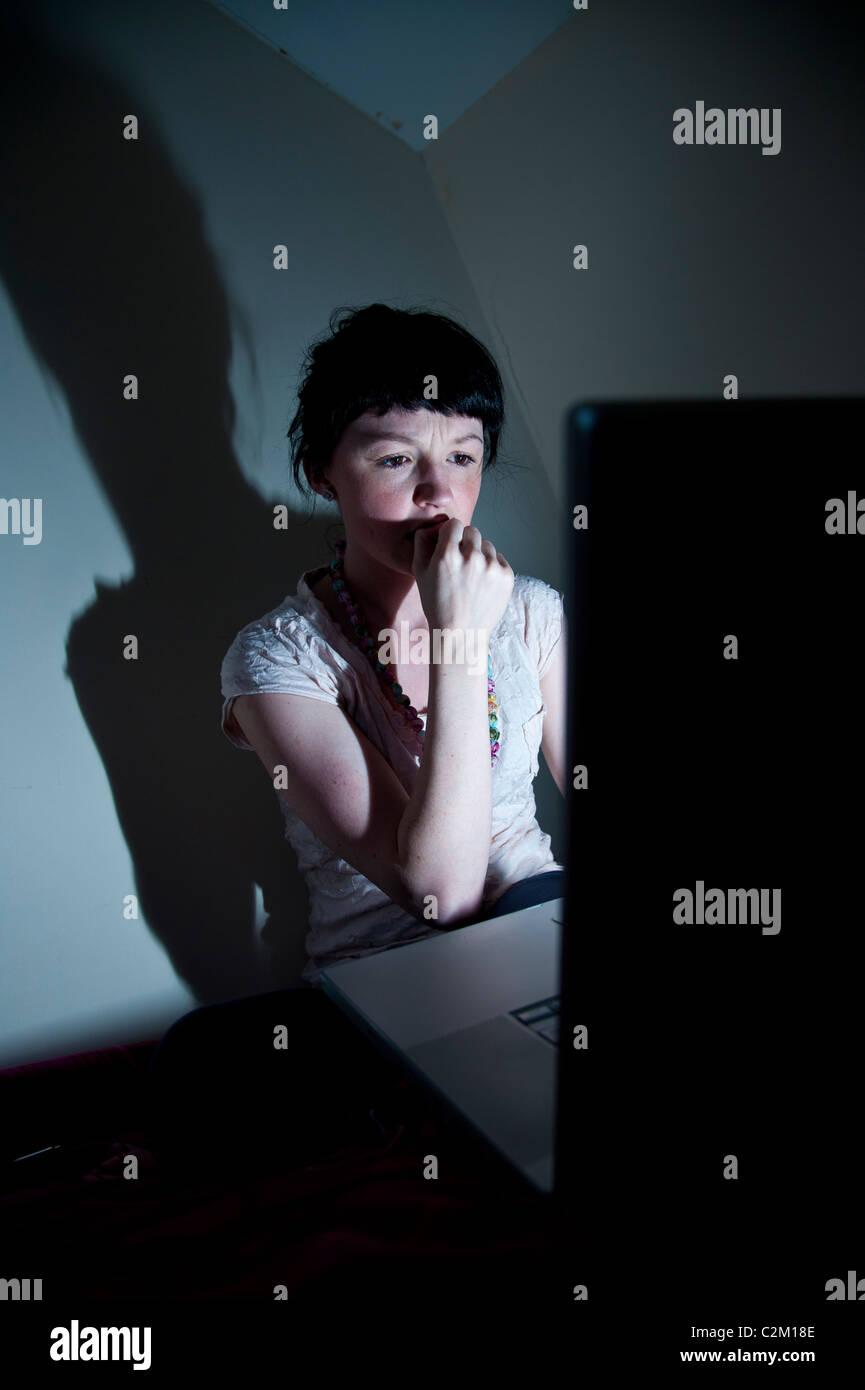 Ein junge Frau UK Student arbeiten auf Laptop-Computer in ihrem Schlafzimmer zu Hause besorgt über e-Mail-Virus Stockbild