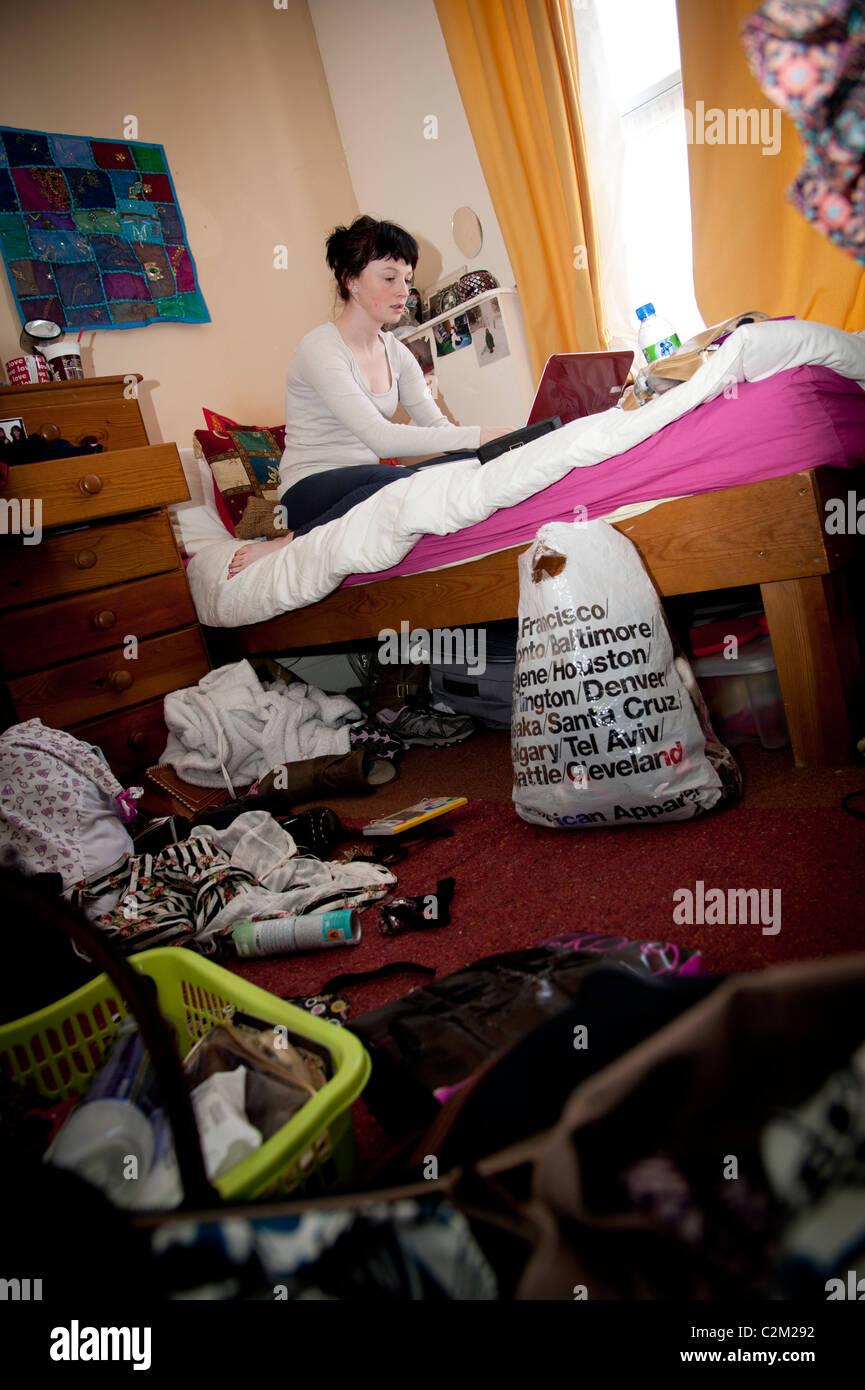 Junge Frau UK Aberystwyth Universitätsstudent arbeiten an ihrem Laptop-Computer in eine unordentliche Schlafzimmer Stockbild
