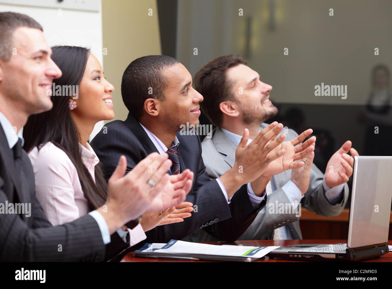 Multi-ethnischen Business-Gruppe begrüßt jemanden mit Händeklatschen und lächelnd. Afrikanisch Stockbild