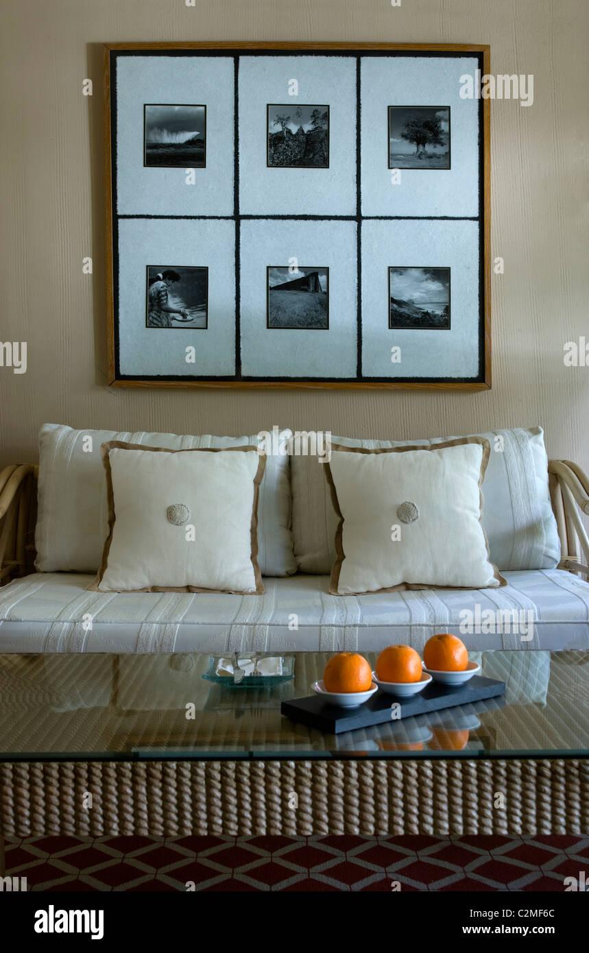 Creme Sofa und Kissen unter sechs Fotografien in einem frame Stockbild