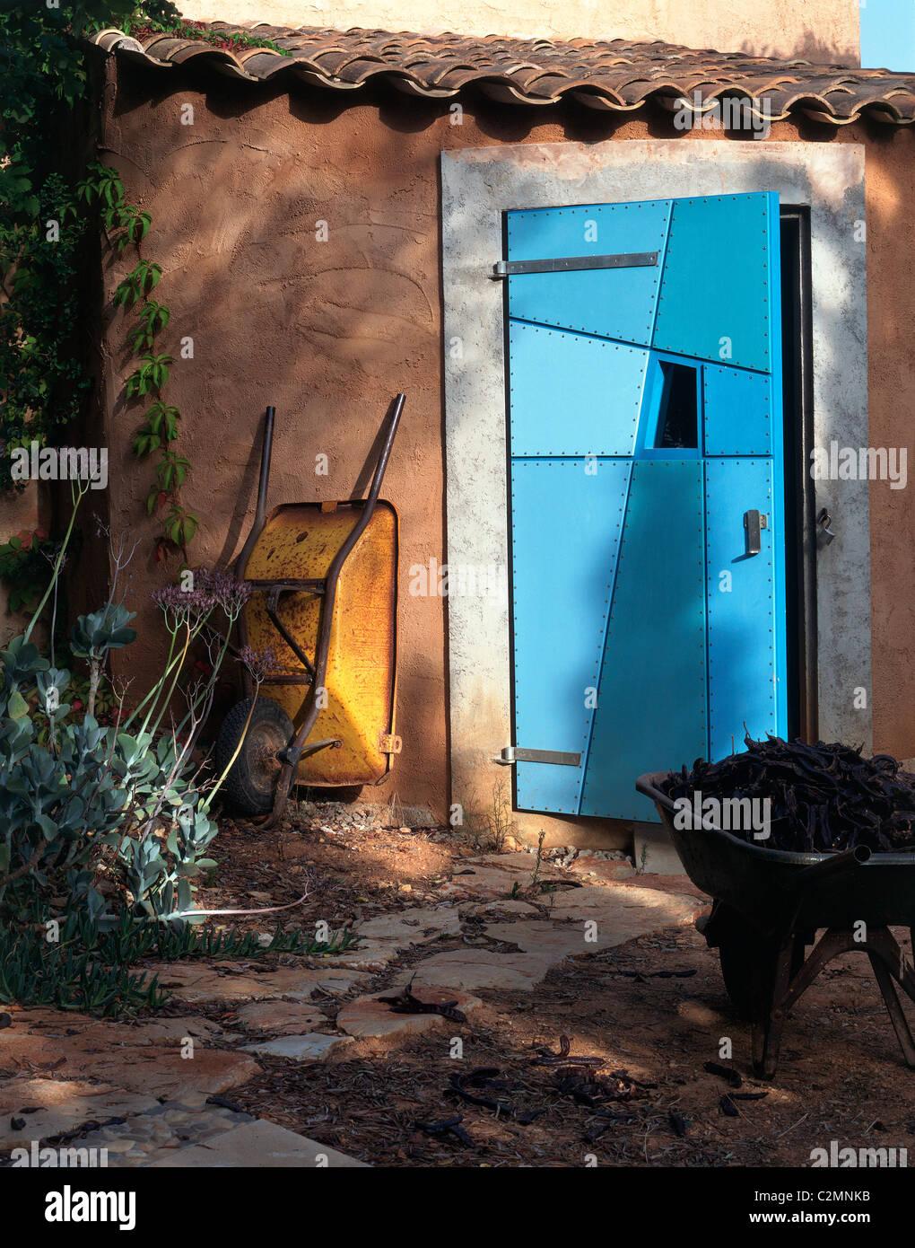 Gelbe Schubkarre außerhalb schrulligen blau Patchwork Schuppen Tür Stockbild