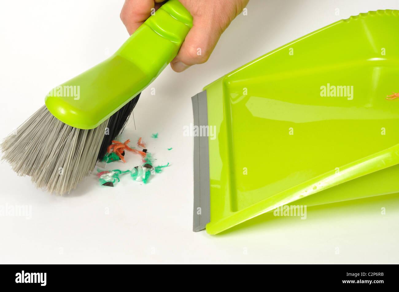Grünen Pinsel und Kehrschaufel mit einigen Müll auf weißem Hintergrund Stockbild