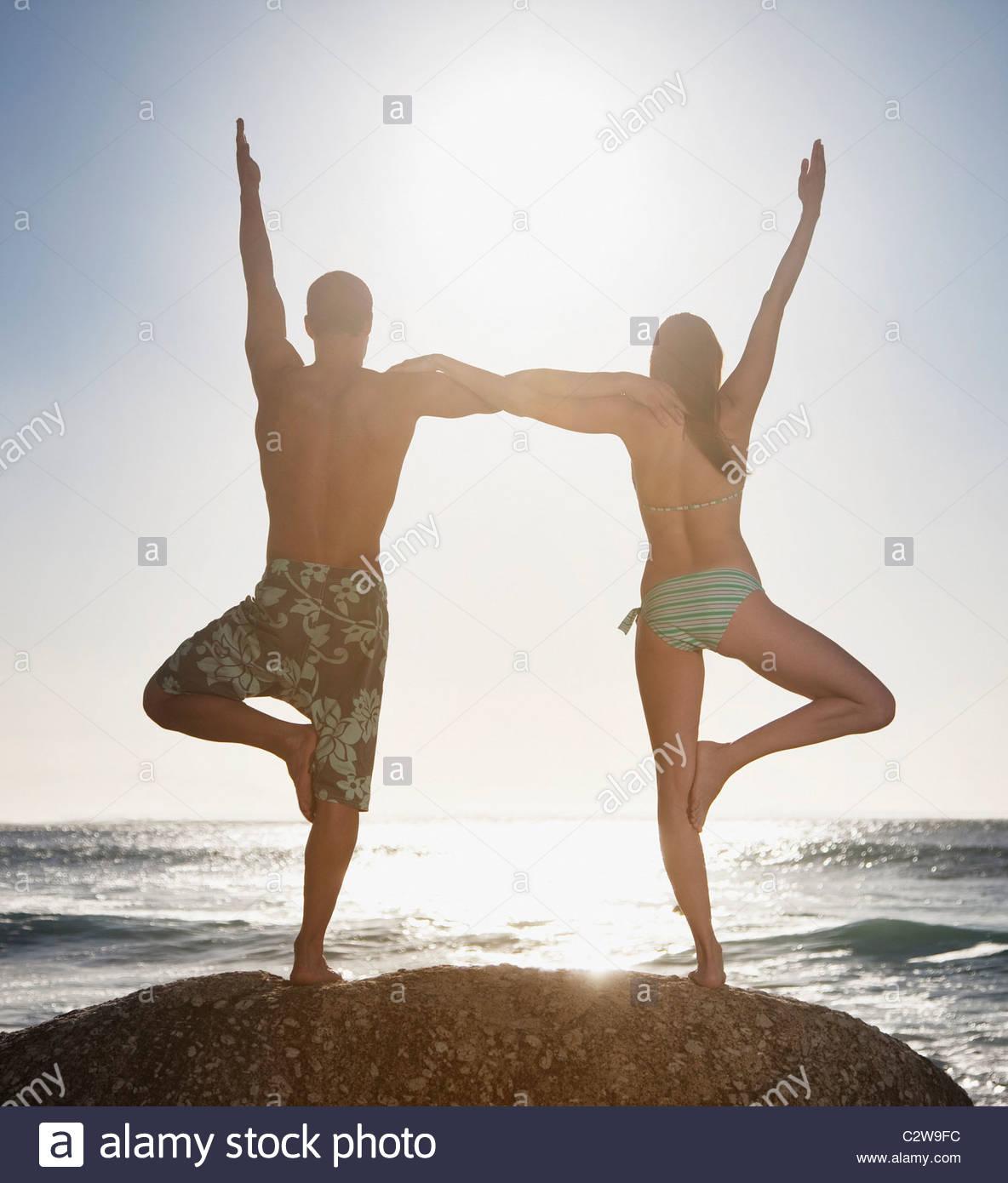 Paar, balancieren auf einem Bein zusammen am Strand Stockfoto