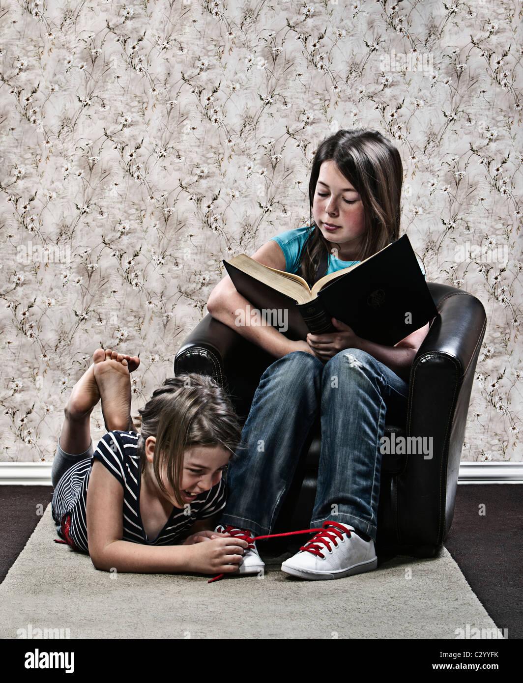 Mädchen, die Schnürsenkel der Schwester zu binden, während sie ein Buch liest Stockbild