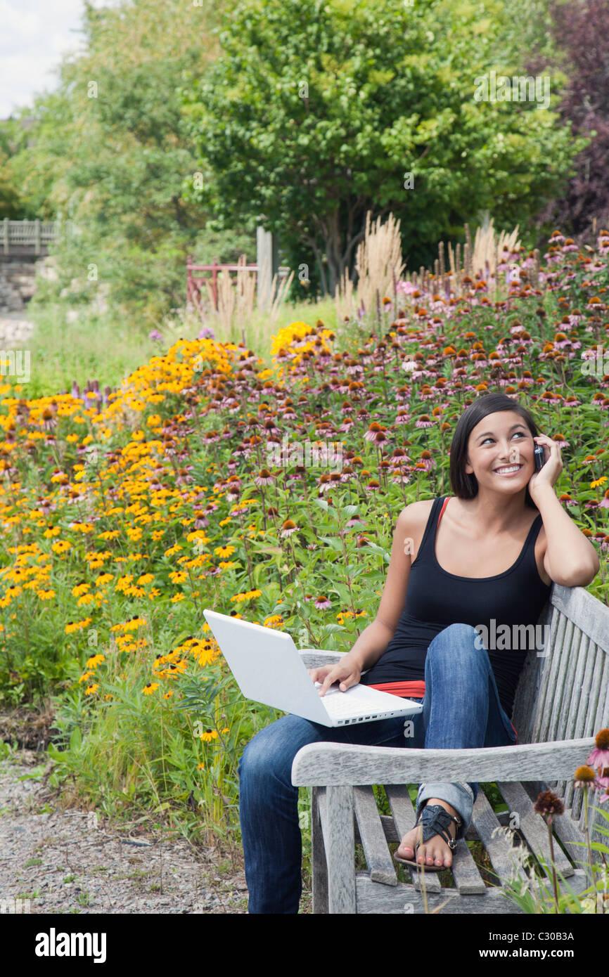 Attraktive Asiatin Handy Laptop Kommunikation im Gespräch Stockbild
