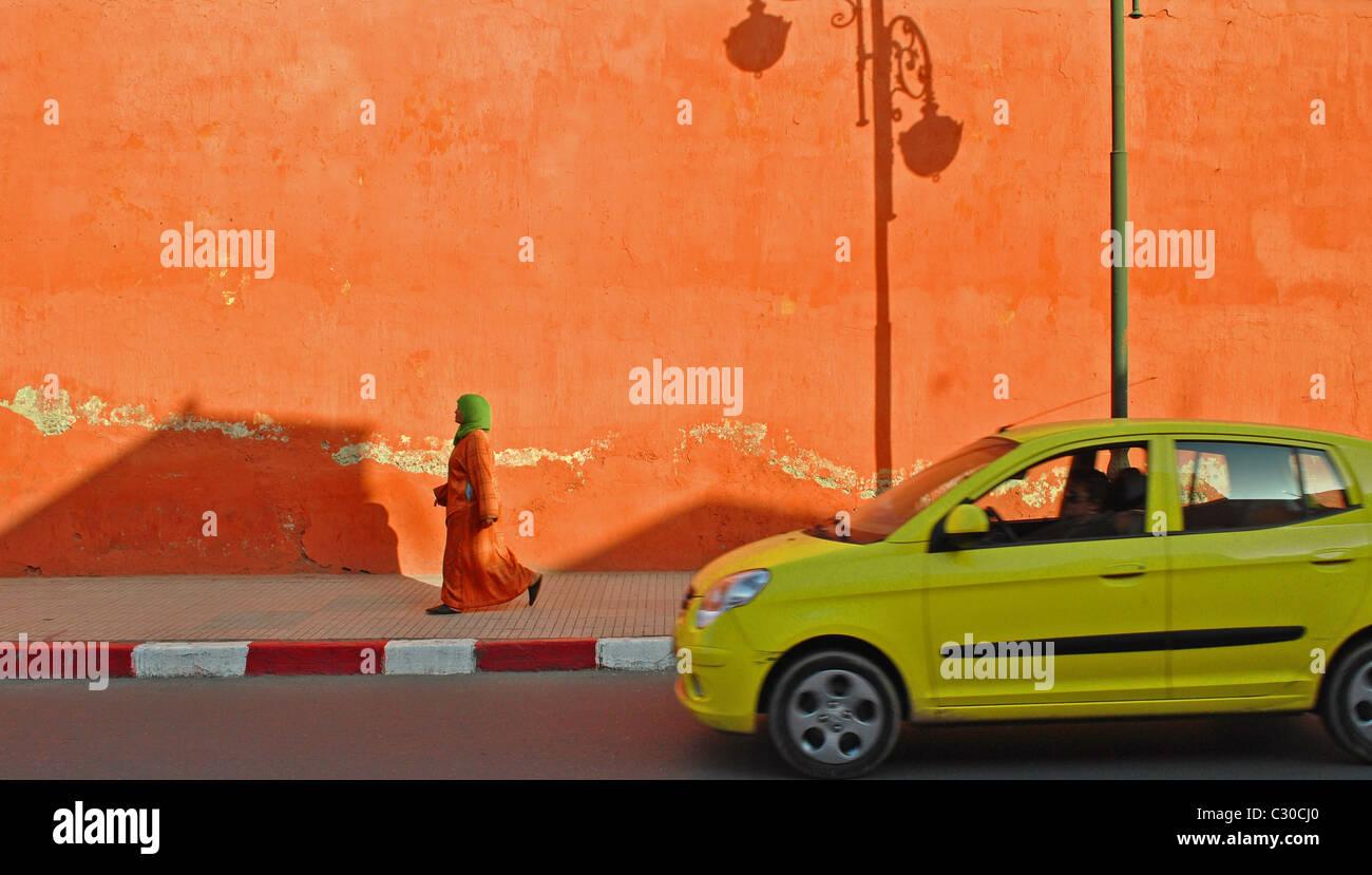 Eine Frau und Auto passieren durch den Schatten von einem Laternenpfahl an einer bunten Wand in Marrakesch, Marokko Stockbild