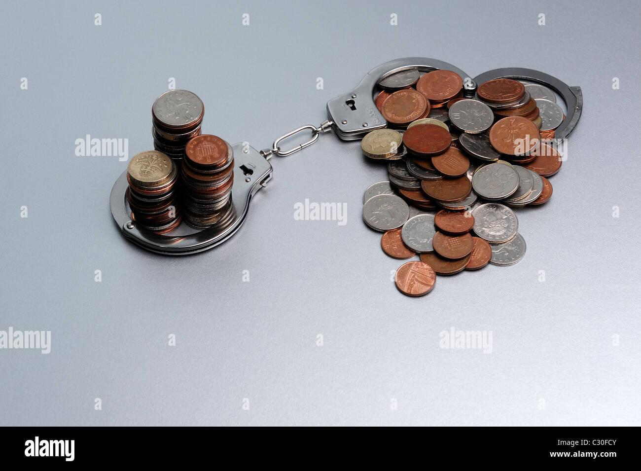 Münzen in Handschellen Stockfoto