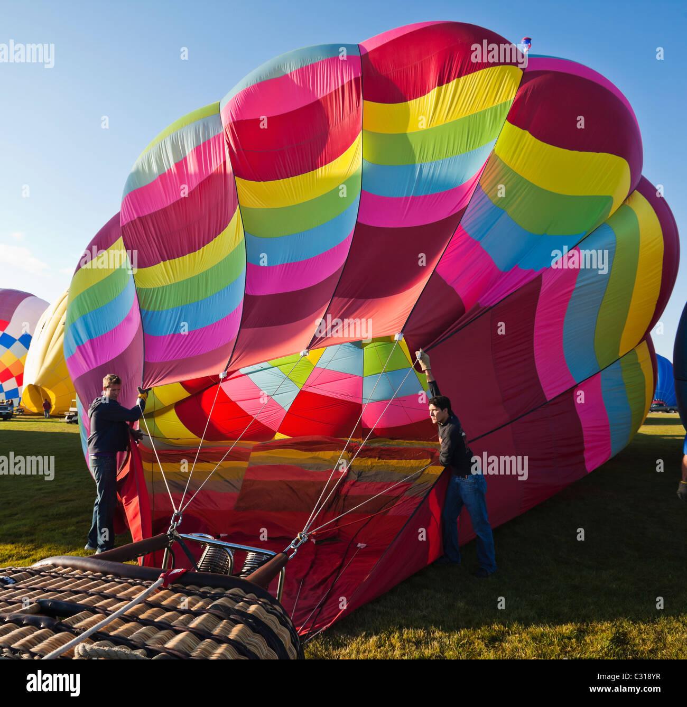 Zwei Männer halten den Ballon öffnen, wie es mit Luft füllt. Albuquerque, New Mexico, USA. Stockfoto
