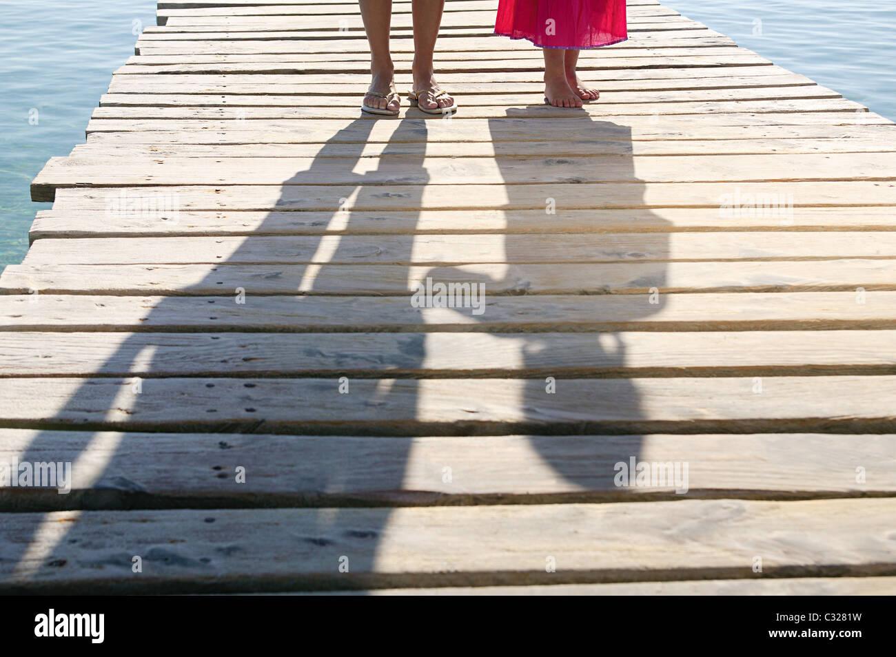 Schatten der Kinder und Erwachsene auf Steg Stockbild
