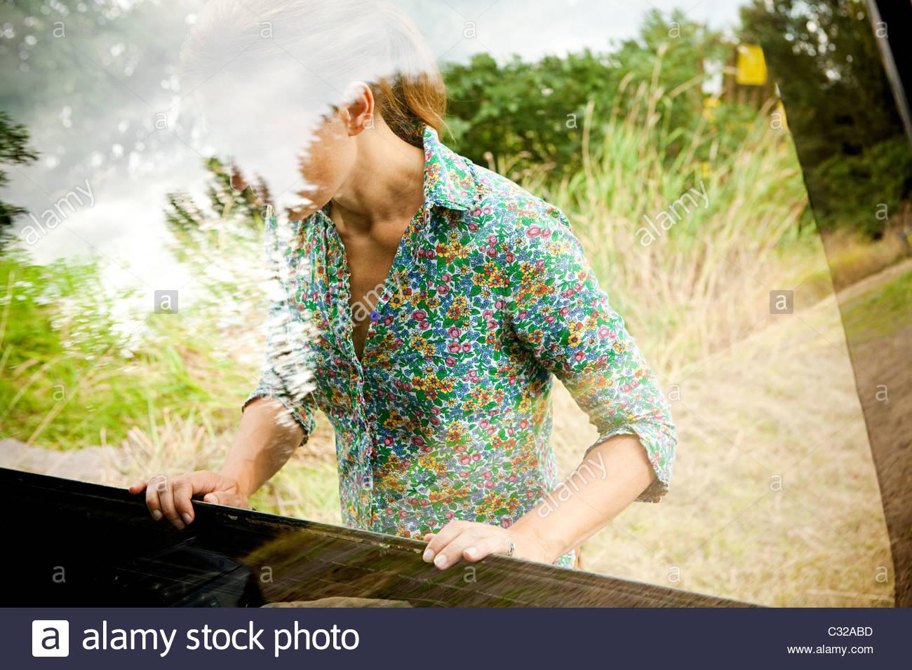 Frau, die durch ein Autofenster betrachtet Stockbild
