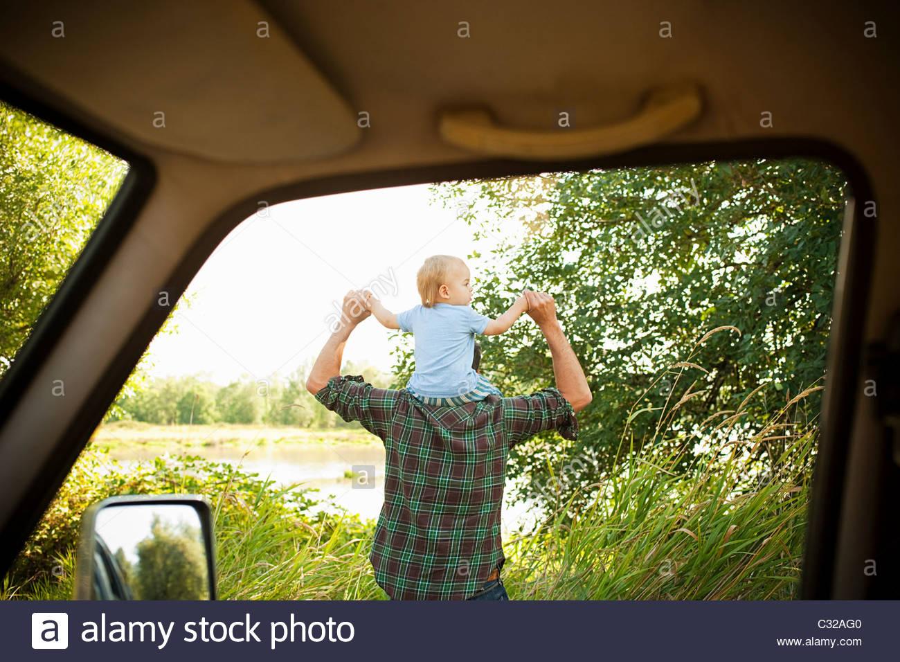 Vater mit Sohn auf Schultern, von einem Auto gesehen Stockbild