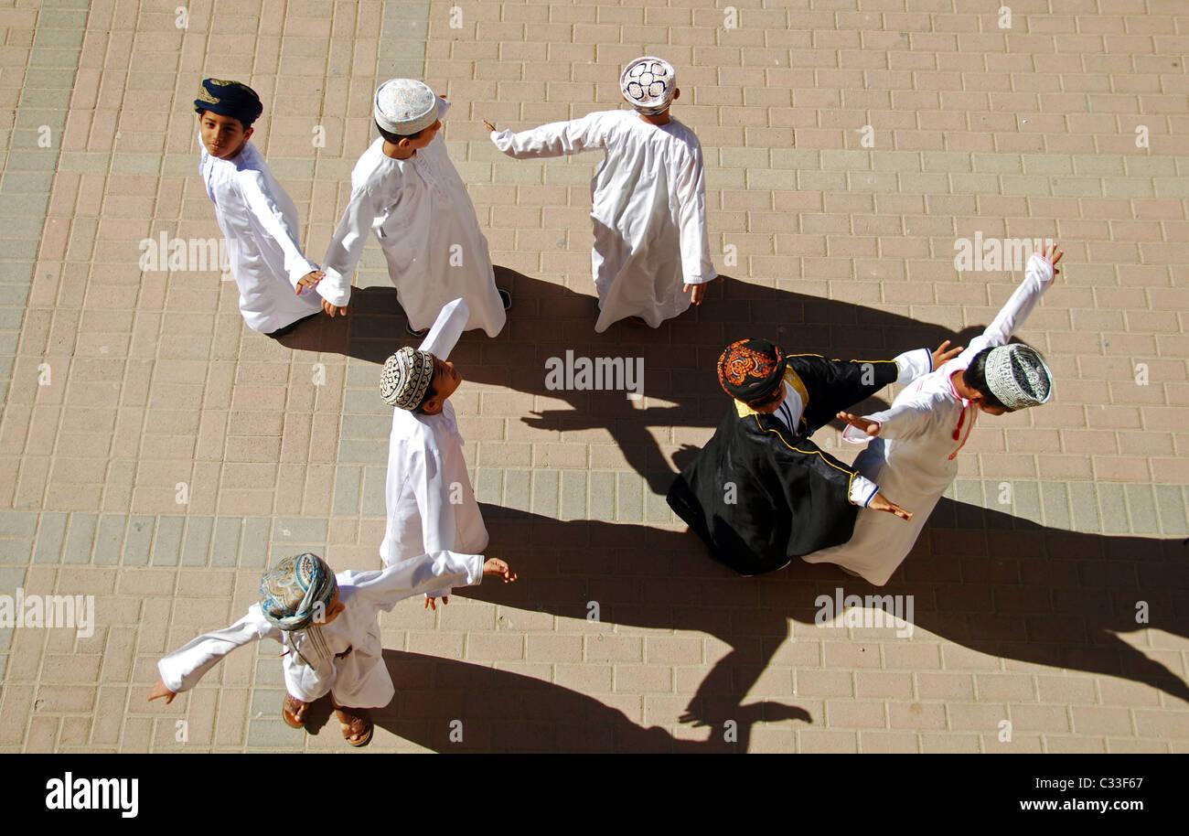 Oman, Maskat, Draufsicht von Schuljungen mit Armen heraus stehen und tanzen auf dem Boden an einem sonnigen Tag Stockbild