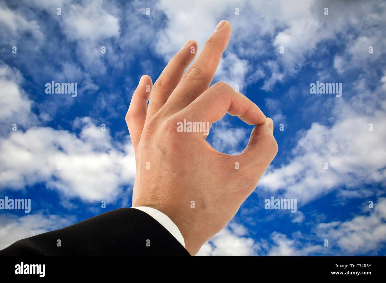 Business-Mann die hand Unterzeichnung in Ordnung am Himmel Stockbild