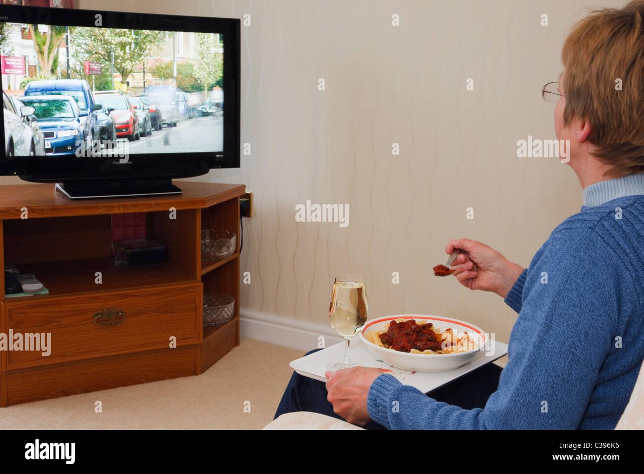 Alltägliche Szene einer reifen Frau alleine vor dem Fernseher essen ein Abend TV Mahlzeit mit einem Glas Wein Stockbild