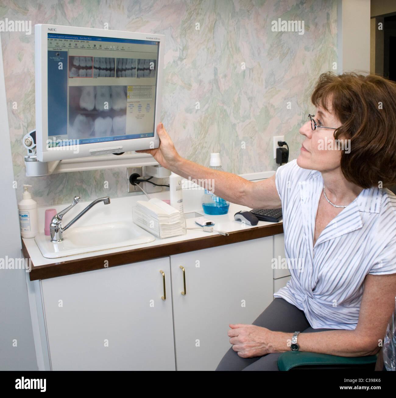 Frau Zahnarzt Zähne des Patienten auf dem Computerbildschirm zu studieren. St Paul Minnesota MN USA Stockbild