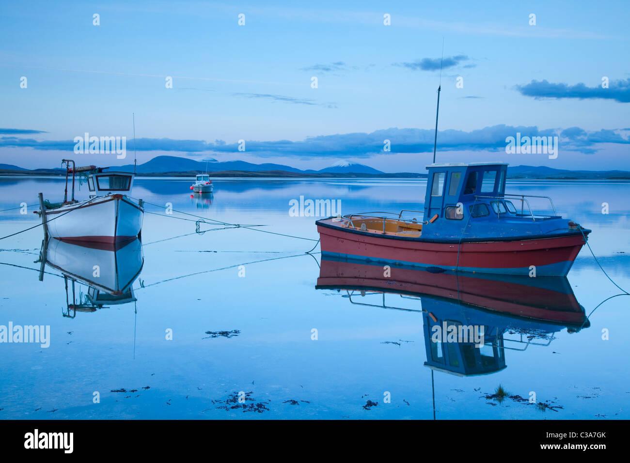 Angelboote/Fischerboote spiegelt sich in der Abenddämmerung in Clew Bay, County Mayo, Irland. Stockbild
