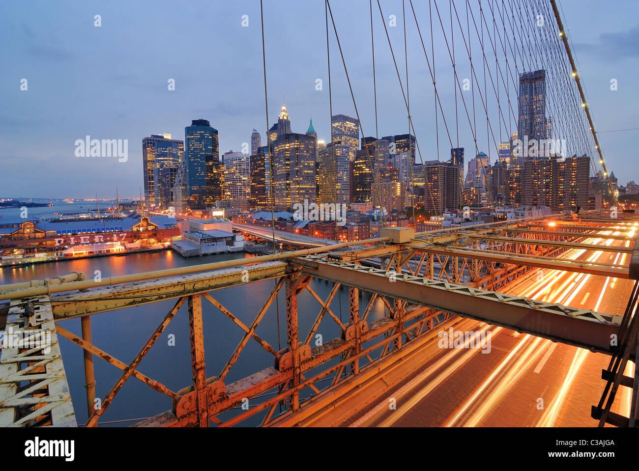 Blick auf Downtown Manhattan von der Brooklyn Bridge mit dem Verkehr von fliegen. Stockbild