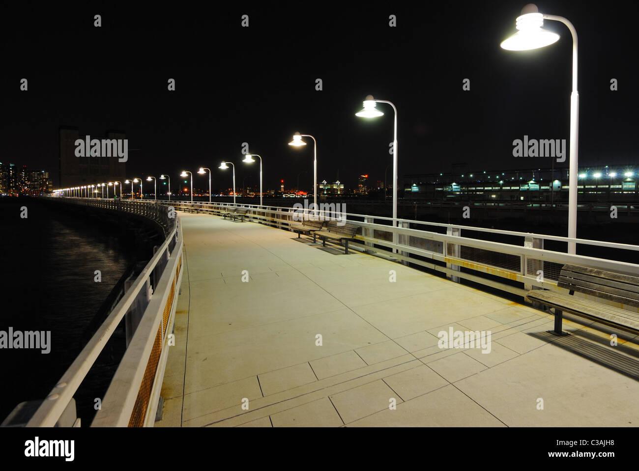 Langen Pier mit Lichtern in der Ferne. Stockbild