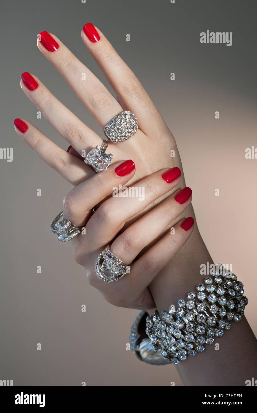 Nahaufnahme von Frauenhand mit rotem Nagellack und Diamant-Schmuck ...