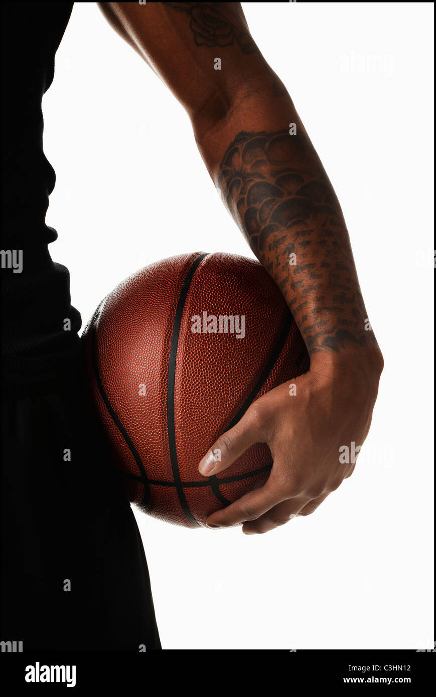 Mittelteil der tätowierte Mann hooding basketball Stockfoto