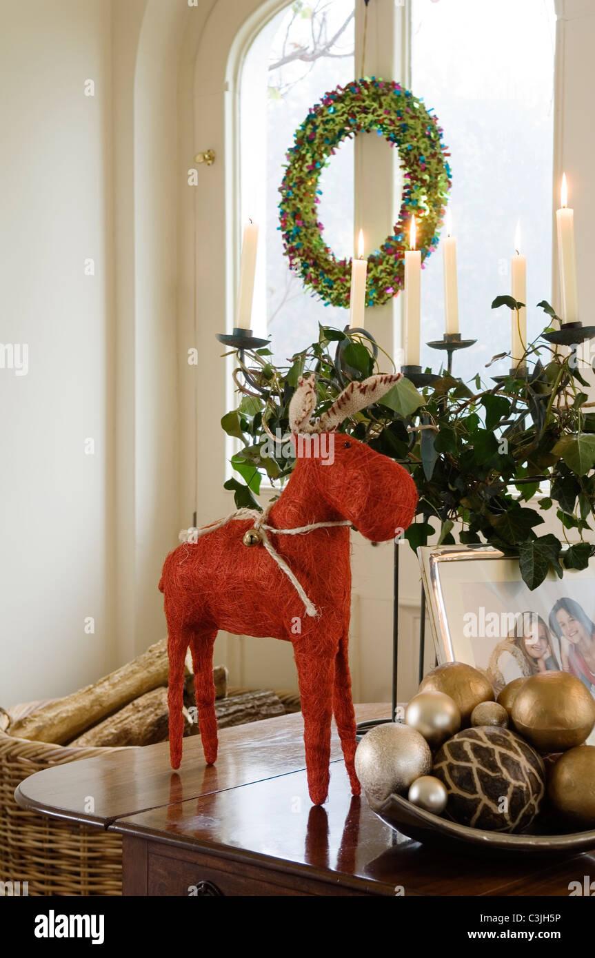 Rentier Weihnachtsdekoration auf Tischplatte mit Kugeln und festliche Kerze Anordnung gewebt Stockbild
