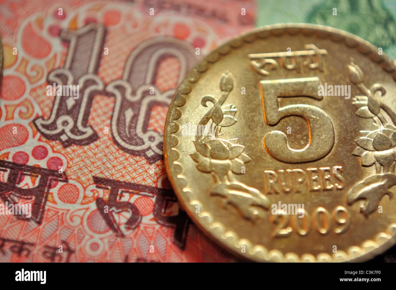 Indische Währung, eine Münze von Rs. 5 und im Hintergrund ein Hinweis von Rs. 10 Stockbild