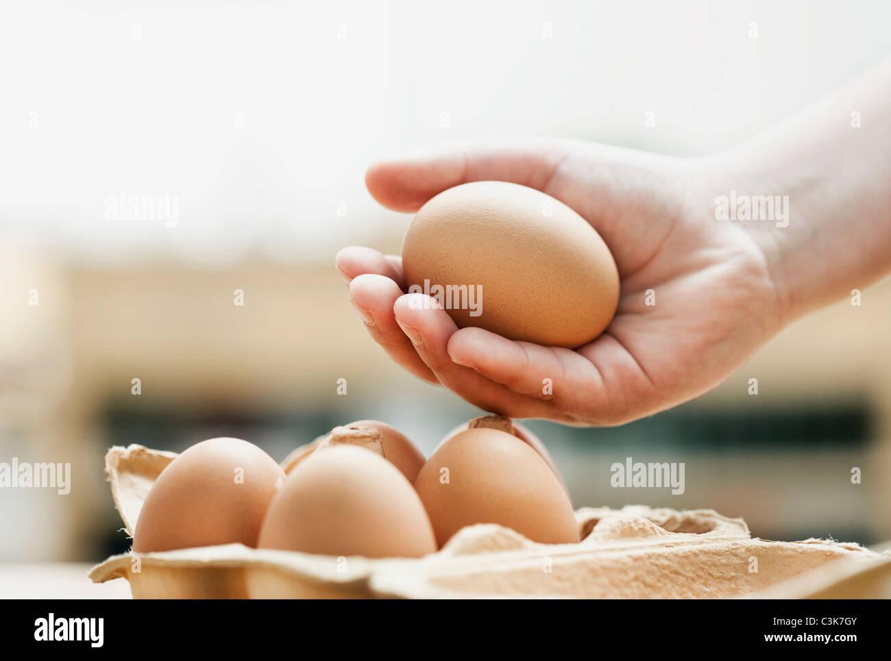 Deutschland, Köln, menschliche Hand mit Eiern, Nahaufnahme Stockbild