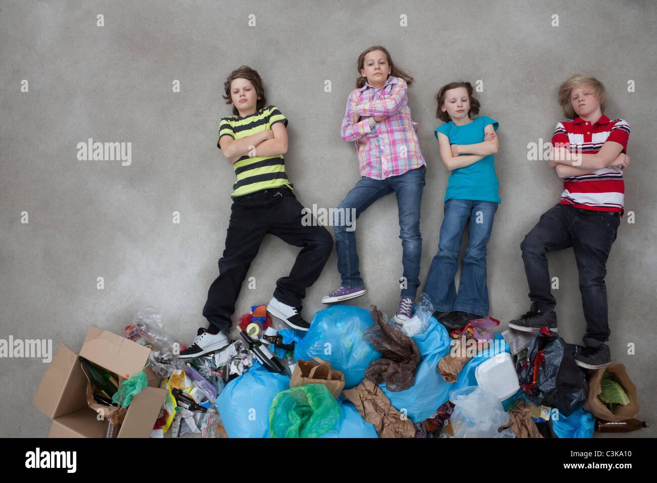 Kinder auf Stapel von Müll und Ökologie-Symbol anzeigen Stockbild